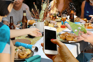 Uber Cyber Freaks – Technology -v- The Real Thing - photo of phone use at a dinner party