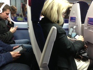 It's so funny - how we don't talk any more. Photo of texting on train