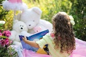 Matthew Effect - photo of child reading to teddies