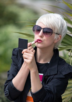 What does watching a reality show say about you? Photo of woman applying lipstick in a mirror